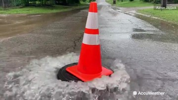 Traffic cone 'surfs' on top of flooded manhole
