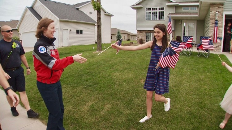 Sydney Dutton greets first responders with flags