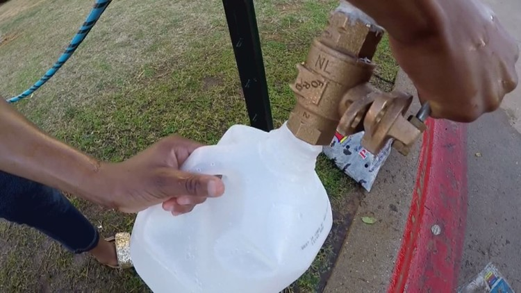 Arlington apartment residents getting water from a fire hydrant as they wait for burst pipes to be repaired