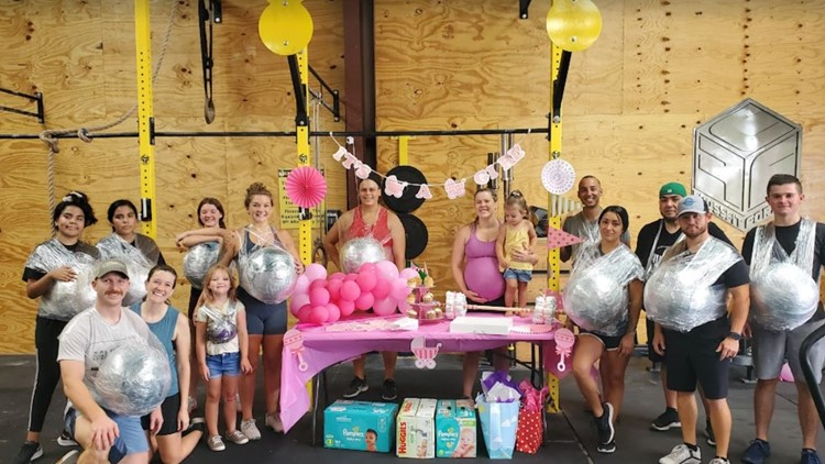 Using medicine balls and plastic wrap, a local gym had an expecting mom in stitches with surprise 'baby workout'