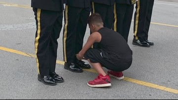 Boy helps Arlington Honor Guard tie his shoe during Fourth of July parade