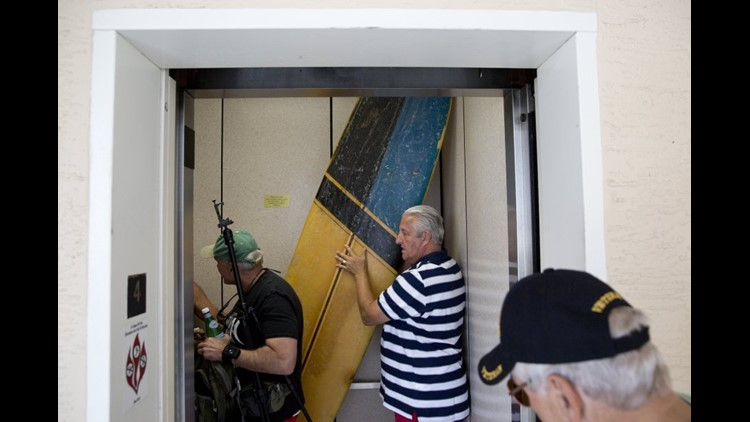The four former Marines load up to head to Cinnamon Beach in Palm Coast, Fla., as Bob Falk squeezes the surfboard, essential to the recreation of the photo, onto the elevator April 23, 2016. (Photo: Luke Franke, Naples (Fla.) Daily News)