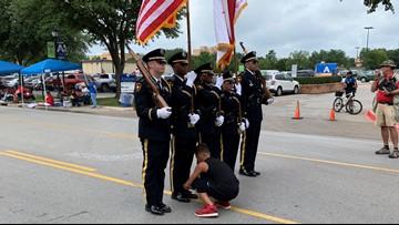 Boy helps Arlington Honor Guard tie his shoe during parade